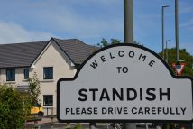 Picture of the standish parish line sign with development in the background
